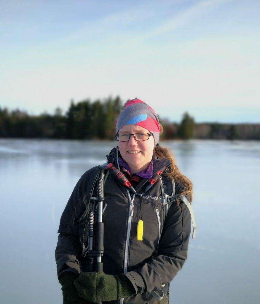 Syntolkning: En porträtt bild på Hanna. Blurrig bakgrund med frusen sjö och granskog. Hanna har isdubbar och ispik med sig och kisar lite mot solen.