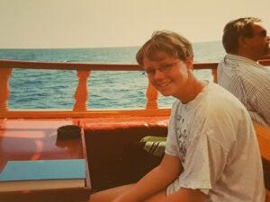 Hanna tittar leende in i kameran. I bakgrunden syns havet med små vågor på och båtens reling. På bordet framför henne står ett askfat. Bakom henne sitter en man i solglasögon.